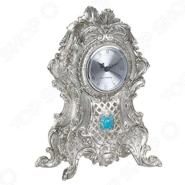 Часы настольные Rosenberg 3901 оригинальные часы в металлическом корпусе с никеле-серебряным покрытием. Имеют ажурное оформление, с приятной детализацией, которое дополнено красивым голубым камнем по центру. Опираются часы на 4 прочные ножки. На циферблате отображены римские цифры и стрелки часов, минут и секунд с оформлением под корпус часов. Такие часы будут отлично смотреться с любым интерьером, а также станут прекрасным подарком для близкого человека. Работают от 1 батарейки типа АА не входит в комплект .