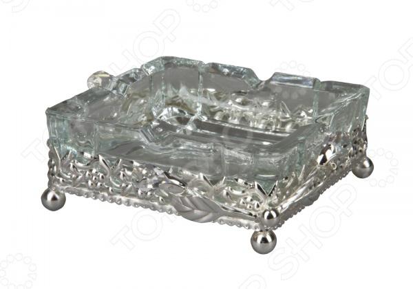 Пепельница Rosenberg оригинальная пепельница квадратной формы. Выполнена из качественного плотного стекла и металла со специальным покрытием. Металлическая подставка имеет 4 опорные ножки и ажурное оформление с дополнением в виде граненного стекла, которое будет красиво переливаться при вечернем освещении. Такая пепельница будет прекрасно смотреться на любом столе. Пепельница легко очищается под проточной водой. Идеальное решение как для дома, так и для кафешек или ресторанов.