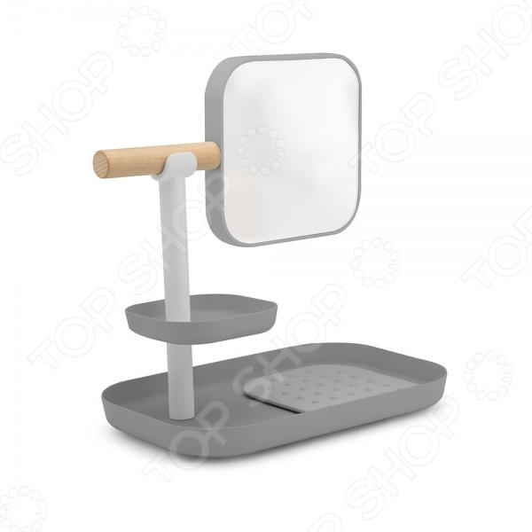 Зеркало косметическое на подставке Umbra VanaЗеркала<br>Зеркало косметическое на подставке Umbra Vana это современный, удобный и очень практичный органайзер. Поможет представительницам прекрасного пола сделать ежедневные процедуры, связанные с нанесением косметики, легче и приятнее. Представленная модель оснащена съемным зеркалом, двумя нишами и специальным ковриком с рельефной поверхностью. Теперь все мелкие предметы и косметические принадлежности найдут свое место, а при желании их можно переносить одновременно вместе с подставкой.<br>