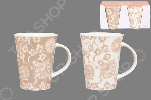 Набор кружек Elan Gallery «Цветы»Кружки. Чашки<br>Набор кружек Elan Gallery Цветы изготовлен из высококачественной керамики и украшен изысканным рисунком. Посуда из этого материала позволяет максимально сохранить полезные свойства и вкусовые качества воды. Крепкий, ароматный кофе или чай, заваренный в представленных кружках, придаст заряд бодрости, позитива и энергии на весь день! Классическая форма и насыщенная цветовая гамма изделий позволят наслаждаться любимым напитком в атмосфере еще большей гармонии и эмоциональной наполненности. Объем одной кружки составляет 320 мл. Набор кружек Elan Gallery Цветы является прекрасным подарком для ваших любимых, родных и близких. В наборе поставляются 2 кружки.<br>