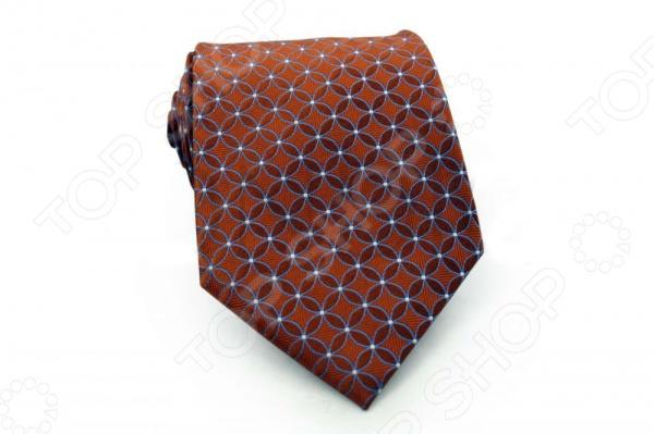 Галстук Mondigo 44460Галстуки. Бабочки. Воротнички<br>Галстук - важный элемент гардероба в жизни каждого мужчины. Сегодня сложно себе представить современного делового мужчину без галстука и это не удивительно, ведь именно галстук является главным атрибутом делового стиля. Не редко, для делового мужчины галстук - одна из немногих деталей, которая позволяет выразить свою индивидуальность, особенно в случаях, когда необходимо соблюдать строгий дресс-код. Однако, галстук уже давно вышел за пределы деловой сферы. Сегодня многие мужчины предпочитающие стиль кэжуал, так же активно прибегают к помощи различных галстуков для создания своего уникального образа. Галстуки стали очень разнообразными как по виду и цвету, так и по форме и материалу изготовления, благодаря этому их можно активно носить не только в офис и на деловых встречах, но даже на отдыхе и в повседневной жизни. Галстук Mondigo 44460 - оригинальная модель, которая станет завершающим штрихом в образе солидного мужчины. Правильно подобранный галстук позволяет эффектно выделить выбранный вами стиль, подчеркнуть изысканность и уникальность его владельца. Стильный мужской галстук ручной работы из шелка высокого качества терракотового цвета, из фактурной ткани, украшен абстрактными геометрическими узорами. Края обработаны лазерным методом. Ширина у основания 8,5 см.<br>