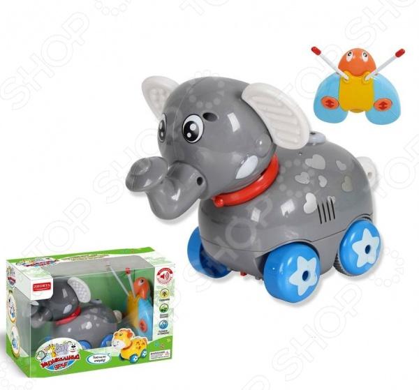 Игрушка радиоуправляемая Zhorya «Музыкальный друг. Слон»Другие радиоуправляемые игрушки<br>Игрушка радиоуправляемая Zhorya Музыкальный друг. Слон прекрасная игрушка для любознательных и активных малышей. Оригинальная развивающая игрушка выполнена в виде небольшого слоника, который ведет себя совсем как настоящий. Он также любит играть, ездить вперед, назад или разворачивать направо и налево. Управлять его движением можно при помощи специального пульта. У слона также двигается голова. Игрушка изготовлена из высококачественных материалов, которые не содержат вредных веществ и абсолютно безопасны для детского здоровья. С такой занимательной игрушкой ваш ребенок сможет развить внимательность, координацию и воображение. Также предусмотрены звуковые и световые эффекты.<br>