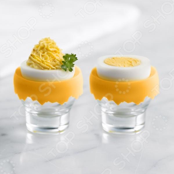С подставкой для яиц Trudeau Яичный трон даже привычный с детства завтрак станет чем-то необычным и уникальным. Стеклянная рюмочка утонченной формы имеет силиконовую подставку, которая легко снимается и моется. Силикон плотно прижимает яйцо, чтобы оно не скользило. С такой подставкой те кто любит завтракать сваренными вкрутую или всмятку яйцами, смогут делать это благородно и изыскано на манер истинных аристократов.