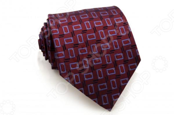 Галстук Mondigo 44310Галстуки. Бабочки. Воротнички<br>Галстук - важный элемент гардероба в жизни каждого мужчины. Сегодня сложно себе представить современного делового мужчину без галстука и это не удивительно, ведь именно галстук является главным атрибутом делового стиля. Не редко, для делового мужчины галстук - одна из немногих деталей, которая позволяет выразить свою индивидуальность, особенно в случаях, когда необходимо соблюдать строгий дресс-код. Однако, галстук уже давно вышел за пределы деловой сферы. Сегодня многие мужчины предпочитающие стиль кэжуал, так же активно прибегают к помощи различных галстуков для создания своего уникального образа. Галстуки стали очень разнообразными как по виду и цвету, так и по форме и материалу изготовления, благодаря этому их можно активно носить не только в офис и на деловых встречах, но даже на отдыхе и в повседневной жизни. Галстук Mondigo 44310 - оригинальная модель, которая станет завершающим штрихом в образе солидного мужчины. Правильно подобранный галстук позволяет эффектно выделить выбранный вами стиль, подчеркнуть изысканность и уникальность его владельца. Мужской галстук из шелка красного цвета, украшен геометрическими узорами в синих тонах, края обработаны лазерным методом. С обратной стороны галстук прострочен шелковой ниткой, что позволяет регулировать длину изделия.Ширина у основания 8,5 см.<br>