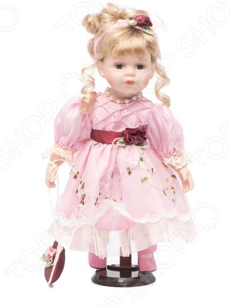 Кукла Angel Collection «Жюли»Куклы<br>Фарфоровые куклы всегда были воплощением красоты, утонченности и изящества. Их история и массовая популяризация началась со стремления Франции окончательно закрепить за собой статус страны-законодательницы мод. В то время куклы использовались в роли уменьшенных манекенов для демонстрации различных нарядов, аксессуаров и косметики. Сегодня же они являют собой настоящие произведения искусства, которые становятся центром музейных экспозиций и знаменитых кукольных коллекций. Кукла Angel Collection Жюли займет почетное место в вашей домашней коллекции. Ее образ изыскан и неповторим, отличается великолепной проработкой и особым вниманием к деталям. Жюли наряжена в пышное розовое платьице и туфельки, ее светлые волосы уложены в красивую прическу. Одежда куклы украшена рюшами, кружевом и атласными розочками.<br>