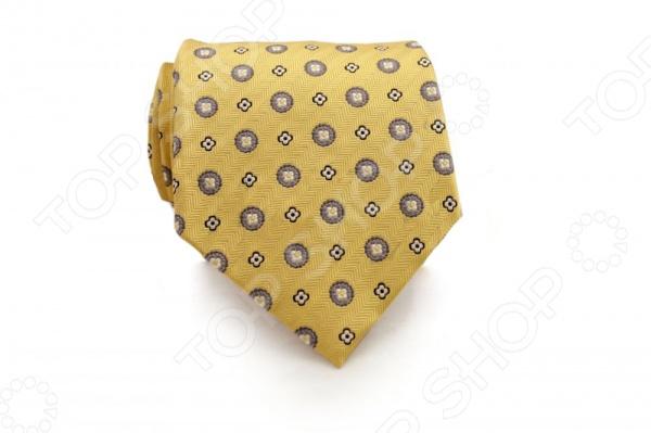 Галстук Mondigo 44390Галстуки. Бабочки. Воротнички<br>Галстук Mondigo 44390 - стильный мужской галстук, выполненный из шелка, который обладает хорошими гигиеническими свойствами и особым блеском. Галстук желтого цвета, украшен цветочно-восточным принтом. Края галстука обработаны лазерным методом. На обратной стороне галстука находится простроченная шелковая нитка, которая позволяет регулировать длину изделию. Такой стильный галстук будет очаровательно смотреться с мужскими рубашками темных и светлых оттенков. Необычный дизайн дополнит деловой стиль и придаст изюминку к образу строгого делового костюма.<br>