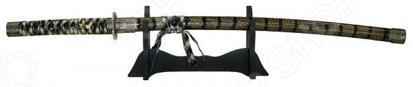 Модель самурайского меча 31137 комплект, состоящий из катаны и стенда для нее. Роскошь, изящество, утонченность форм, завораживающая красота и, исключительно, качественные материалы вот основные достоинства этой модели, которые будут оценены всеми истинными знатоками японской культуры. Если вы коллекционируете холодное оружие или просто хотите оформить интерьер квартиры в восточном стиле, то такая модель самурайского меча вам обязательно пригодится. Лезвие оружия изготовлено из первоклассной стали, устойчивой к коррозии, поэтому повышенная влажность ему не страшна. Однако к деревянному стенду и ножнам следует относиться с особой тщательностью и регулярно протирать мягкой сухой тканью, чтобы удалить пыль. Меч катана настоящее произведение искусства, с любовью созданное умелыми руками мастера. Становясь обладателем такого декоративного оружия, вы получаете уникальную возможность прикоснуться к загадочной культуре Японии, привнести ее частичку в свое жилище и, конечно же, ощутить атмосферу эпохи самураев своими собственными руками.